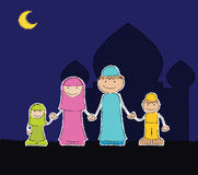 Muslim Family at Mosque. Represent family members of Muslim (father, mother, daughter, and son) with mosque background in the outdoor night Stock Photography
