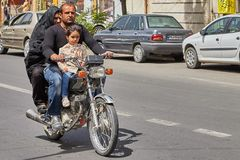 Muslim family on a motorcycle on busy street, Kashan, Iran. Kashan, Iran - April 27, 2017: Muslim family:  man, woman in a hijab and little  girl ride a Royalty Free Stock Image