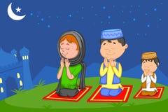 Muslim family offering namaaz on Eid Stock Photo
