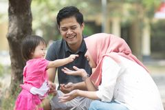 Happy young muslim family playing at park with little girl showing something to her mom in carrier at sunny day stock images