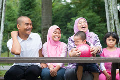 Muslim family outdoor. Happy Southeast Asian family sitting at garden bench laughing together, outdoor lifestyle at nature green park royalty free stock images