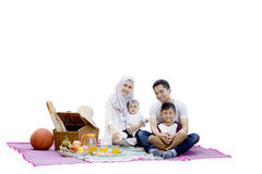 Muslim family with picnic basket. Happy muslim family picnicking together while sitting on mat with picnic basket and foods, isolated on white background Royalty Free Stock Images