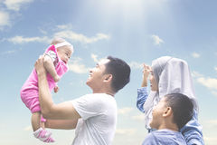 Muslim family playing outside with baby. Picture of cheerful muslim family playing outside together while holding their baby, shot at sunny day Stock Photography