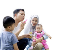 Muslim family playing soap bubbles. Portrait of happy muslim family playing soap bubbles together, isolated on white background Royalty Free Stock Images