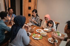 Muslim family pray before dinner. Muslim family pray before having their dinner together at home stock photos