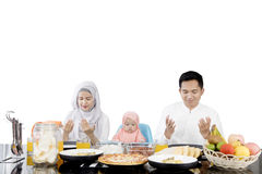Muslim family praying before having meal Stock Images