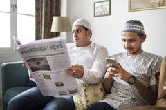 Muslim family reading the news stock photography
