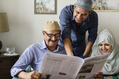 Muslim family reading the news stock images