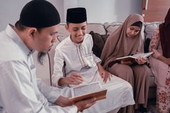 Muslim family reading quran or holy book of islam together. Portrait of happy muslim family reading quran or holy book of islam together stock images