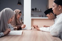 Muslim family reading quran or holy book of islam together. Portrait of happy muslim family reading quran or holy book of islam together royalty free stock images