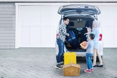 Muslim family ready for holiday. Picture of Muslim family preparing suitcase into a car for holiday while standing together in the garage Stock Photo