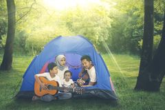 Muslim family relaxed in the tent by playing guitar. Together while camping in the forest stock photo