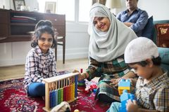 Muslim family relaxing and playing at home stock photos