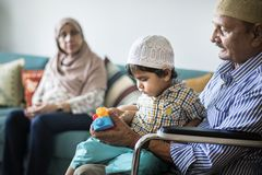 Muslim family relaxing and playing at home stock photo