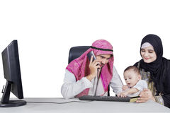Muslim family shopping online together. Image of muslim family paying online with credit card, isolated on white background royalty free stock photo