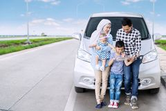 Muslim family holding tablet in the highway. Muslim family sitting in front of their car while holding a digital tablet in the highway Stock Image