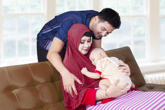 Muslim family sitting on sofa at home Stock Photos