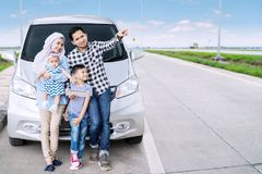 Muslim family with tablet on the highway. Muslim family using a digital tablet and pointing at something while sitting in front of their car on the highway Stock Image