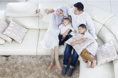 Muslim family taking selfie photo on sofa Royalty Free Stock Images