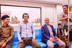 Muslim family travel by metro, Tehran, Iran. Tehran, Iran - April 29, 2017: Muslim family consisting of four men and a girl ride in a subway train car and smile Royalty Free Stock Images