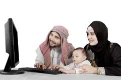 Muslim family using computer over white background. Muslim family using computer isolated over white background royalty free stock images