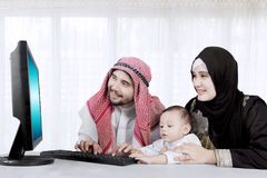 Muslim family using computer online at home royalty free stock images