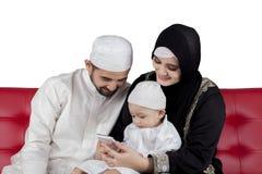 Muslim family using smart phone over white background. Muslim family using smart phone together isolated over white stock photos
