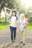 Muslim family walk in park way. Happy muslim family walking in the park way while holding hands and smiling at the camera Royalty Free Stock Image