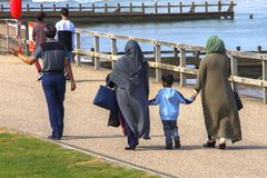 Muslim family walking on the beach stock image