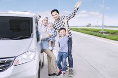 Muslim family waving hands together on the road. Portrait of Muslim family waving hands together at the camera while standing on the road near their car Stock Photos