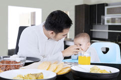 Muslim father feeding his baby. Portrait of a young muslim father feeding his little daughter on the table in dining room at home Stock Photography