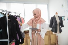 Modern designer sell product online. Muslim female designer using tablet pc to market and check his product online Stock Photography