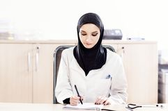 Muslim female doctor fills the medical records Royalty Free Stock Photography