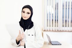 Muslim female doctor standing and holding medical records Stock Photo