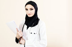 Muslim female doctor in a white coat holding documents Royalty Free Stock Image