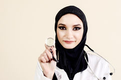 Muslim female doctor in white lab coat holding a stethoscope Royalty Free Stock Photo