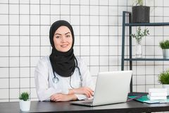 Muslim female doctor writing report on her working desk