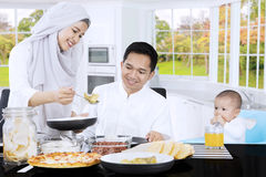 Muslim female serves meal in dining table Royalty Free Stock Photos