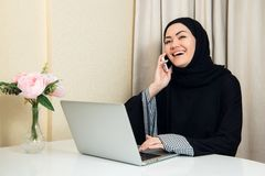 Muslim female talking on the phone while working with laptop computer. royalty free stock photo
