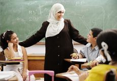 Muslim female teacher with children in classroom. In modern school royalty free stock image