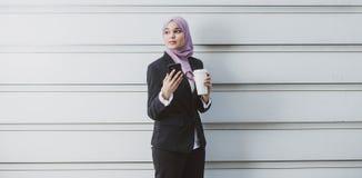 Muslim Female Worker with her smartphone during her coffee break