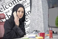 Muslim female worker talking on the phone while working with laptop computer.  Royalty Free Stock Photos