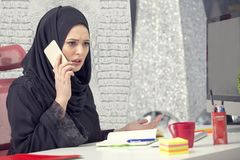 Muslim female worker talking on the phone while working with laptop computer.  royalty free stock photo