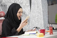 Muslim female worker talking on the phone while working with laptop computer.  stock photo