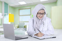 Muslim general doctor works in the clinic. Young muslim female general doctor works in the clinic while writing a medical report with a laptop on the table Royalty Free Stock Images