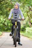 Muslim girl on bicycle Stock Photo