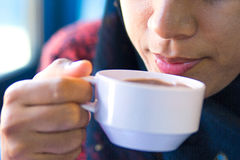 Muslim girl is blowing and sipping hot cocoa. Royalty Free Stock Images