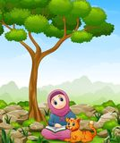 Muslim girl cartoon holding a book and cat in the jungle Stock Photography