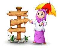 Muslim girl cartoon holding umbrella with blank wood arrow sign Stock Photography