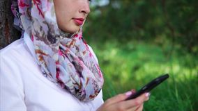 Muslim girl with cell in the park. Muslim girl relaxing outdoor and chatting in online messenger on mobile. Hands view with following close-up portrait of woman stock video